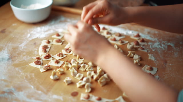 vídeos de stock e filmes b-roll de the woman preparing turkish traditional food mantı (turkish ravioli) - baking bread at home