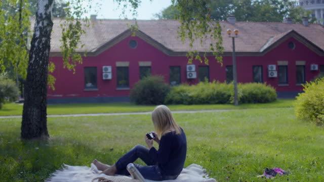 vídeos y material grabado en eventos de stock de la mujer relajarse en el parque en manta y fotografía la naturaleza alrededor de sí misma - memorial day weekend