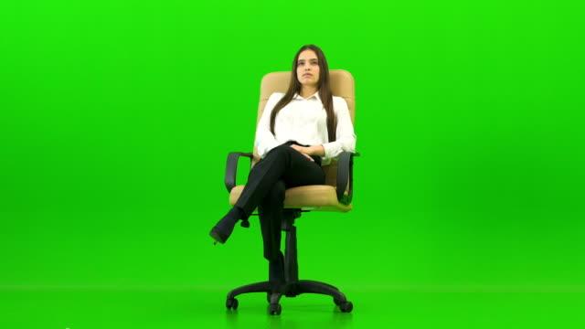 녹색 배경에 사무실의 자에 앉아 여자 - 앉음 스톡 비디오 및 b-롤 화면