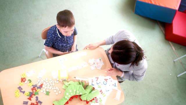 The woman speech therapist and boy patient are learning the correct pronunciation of alphabet letters The attractive woman speech therapist teaches the preschool aged boy to correctly pronunciation a letters and a words. The boy is pronouncing the words. The woman therapist is correcting and helping the boy playroom stock videos & royalty-free footage