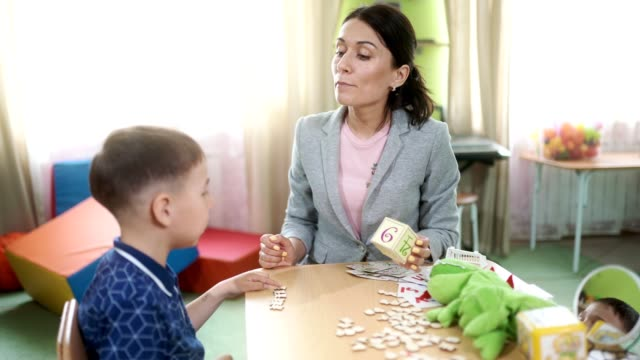 The woman speech therapist and the boy at the therapy session The attractive woman speech therapist teaches the preschool aged boy to correctly pronunciation a letters and a words. The boy is pronouncing the words. The woman therapist is correcting and helping the boy playroom stock videos & royalty-free footage