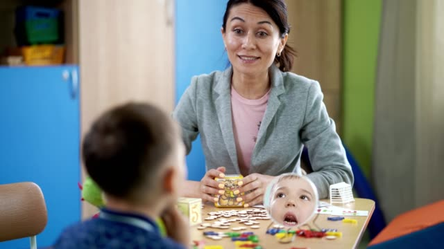 The woman speech therapist teaches the boy on therapy session video