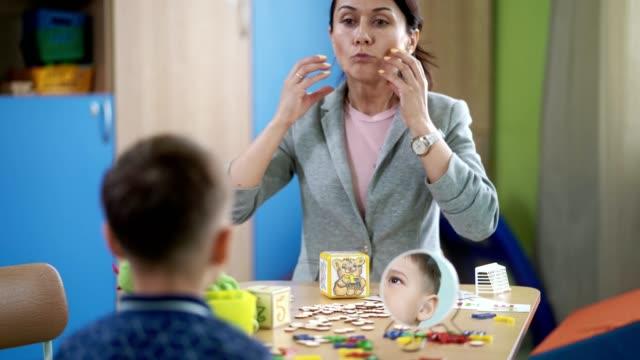 L'orthophoniste femme enseigne le garçon pour corriger la prononciation - Vidéo