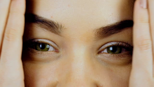vídeos de stock e filmes b-roll de the woman spreads her palms in front of her face and demonstrates her eyes with contact lenses. - contacts