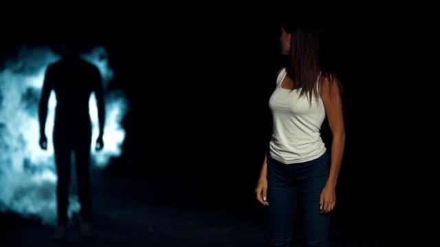 The woman standing in a dark street on a man silhouette background. slow motion