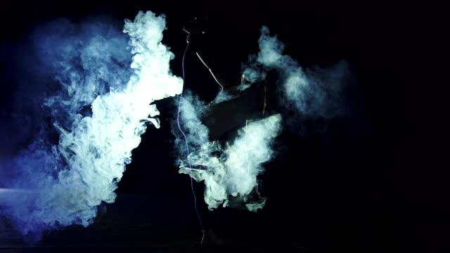 The woman standing in twine in the smoke cloud. night time, slow motion
