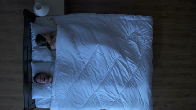The woman wake a snore man in the bed. night time. view from above video
