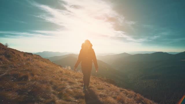 화창한 배경에 산에서 걷는 여자. 슬로우 모션 - mountain top 스톡 비디오 및 b-롤 화면