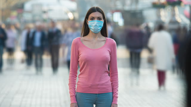 Video The woman with medical face mask stands in the crowded street. time lapse