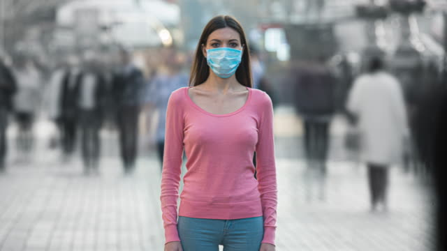 The woman with medical face mask stands in the crowded street. time lapse The woman with medical face mask stands in the crowded street. time lapse traffic time lapse stock videos & royalty-free footage