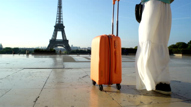 vídeos de stock, filmes e b-roll de a mulher com a mala laranja viajar para paris - moda parisiense