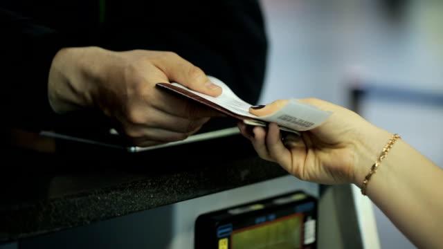 空港で働く女性は、男に必要な書類を与えています。 ビデオ
