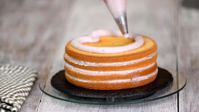 die hände der frau drücken die sahne auf einen kuchen. leckere sahne auf dem kuchen. - sahne stock-videos und b-roll-filmmaterial