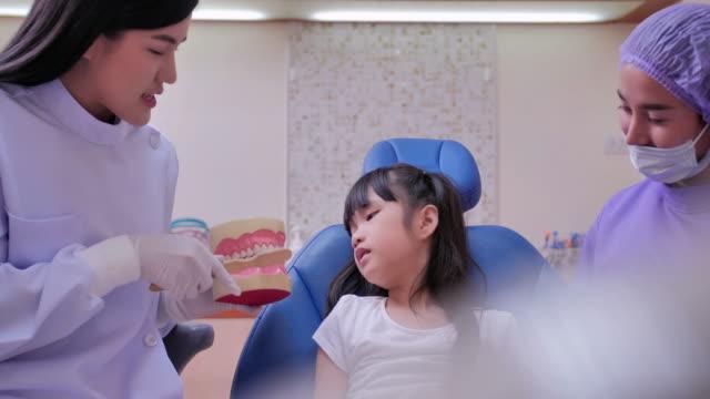 vídeos y material grabado en eventos de stock de la odontóloga de las mujeres está sosteniendo las dentaduras postizas en sus manos y enseñando limpieza modelo de mandíbula dental con cepillo de dientes a la niña escuchar por el dentista. chequeo dental, tecnología, medicina, educación, concepto d - ortodoncista