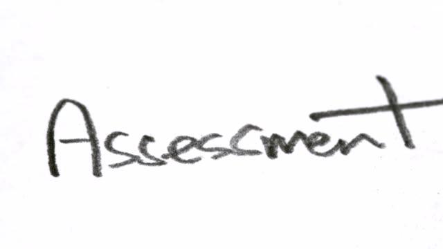 """das wort """"bewertung"""" unten auf papier mit einem bleistift geschrieben - grundschule stock-videos und b-roll-filmmaterial"""
