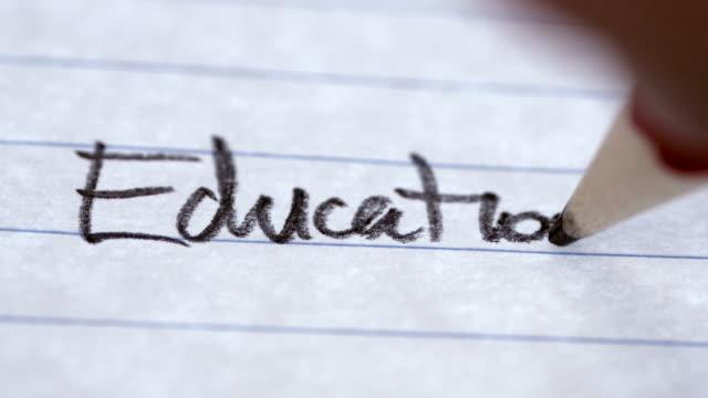 """das wort """"bildung"""" auf liniertes papier in einem notizbuch notiert - grundschule stock-videos und b-roll-filmmaterial"""