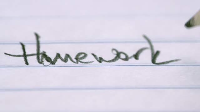 Le mot «Devoirs», écrit sur un bloc-notes dans un gros plan tourné - Vidéo