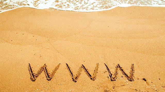 The word www handwritten in sand on a beach video