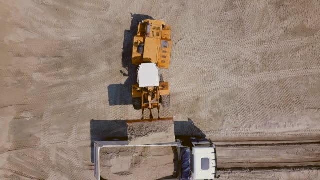 The work of loading equipment in the sand quarry Loading, transportation and unloading of sand from the quarry by a loader into the body of a dump truck. on a sunny day. aerial view, frame from a drone dump truck stock videos & royalty-free footage