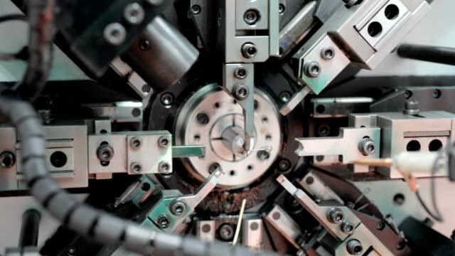vídeos de stock, filmes e b-roll de o trabalho do mecanismo de cnc, máquina de dobra. fabricação de uma mola de arame. panning circular da esquerda para a direita - automatizado