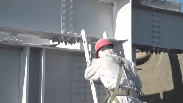 The worker in a protective suit paints with white paint building constructions.