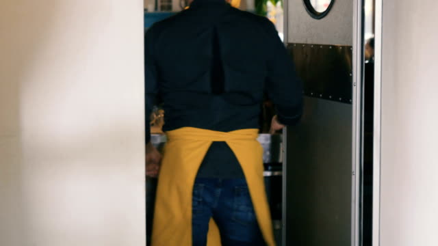The worker in apron open the door and go in working place video