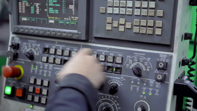 The worker presses the buttons of the old control panel with the display Close-up of the hand of a man working pressing the buttons of the old control panel with the display. Equipment at the machine-building plant manufacturing equipment stock videos & royalty-free footage