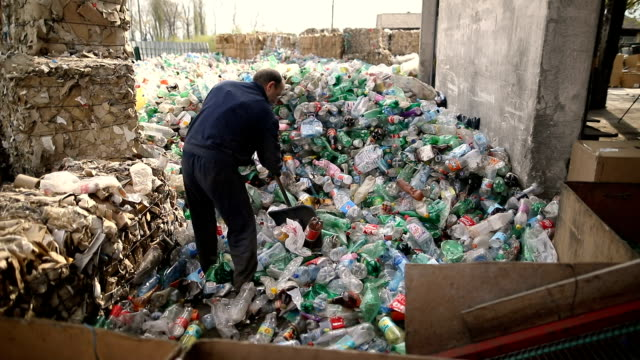 The worker pushes plastic bottles with a shovel for recycling.Working at a recycling factory