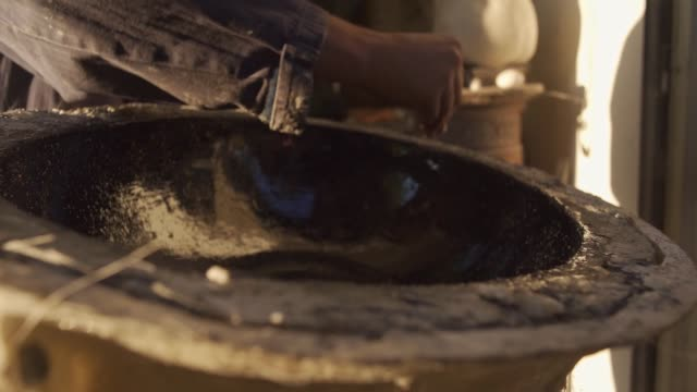 The worker spills glitter on future black wash bowl as a little detail