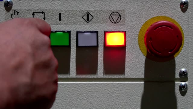The worker's hand switching on the machine start button, close up