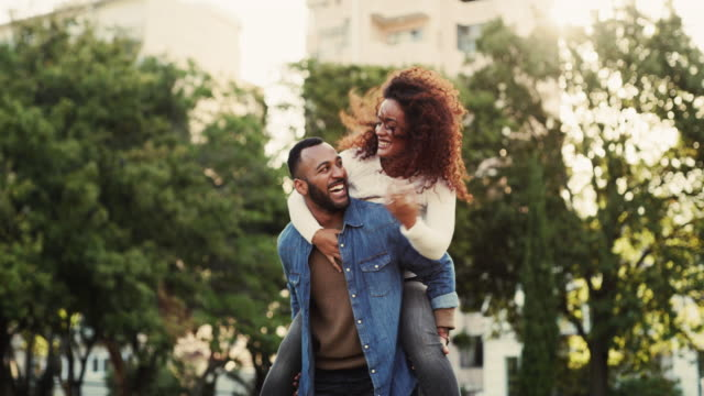 The world needs more love like theirs 4k video footage of a happy young couple enjoying a piggyback ride in the park girlfriend stock videos & royalty-free footage