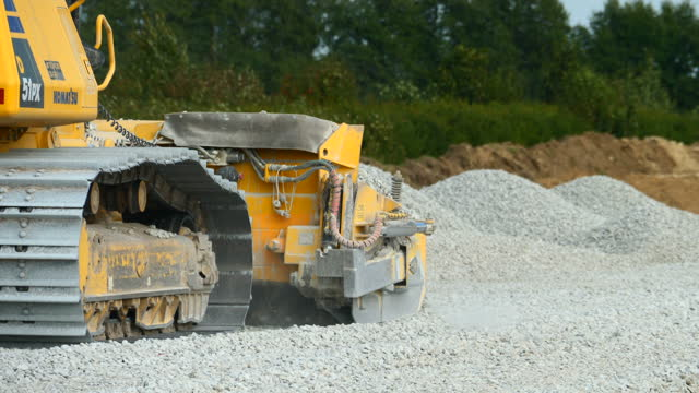 The yellow bulldozer in the industrial site The yellow bulldozer in the industrial site grabbing some gravel on the ground construction machinery stock videos & royalty-free footage