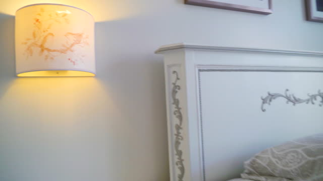 The yellow lampshade on the side of the bed inside the bedroom The yellow lampshade on the side of the bed inside the bedroom with the purple color bedsheet and the towels on the top lamp shade stock videos & royalty-free footage