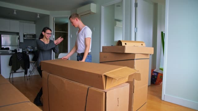 The young 30 years old man and teenager girl unboxing and assembling furniture in the new apartment video