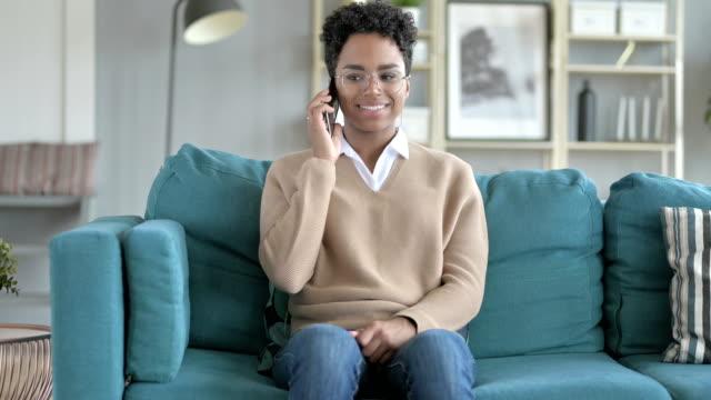 la giovane ragazza africana che parla al telefono mentre è seduta sul divano - rispondere video stock e b–roll