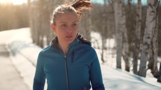 the young athletic woman running on a mountain road during sunny winter days. - stock video - rozgrzewka filmów i materiałów b-roll