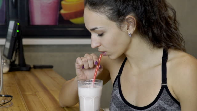 The young beautiful woman drinks milkshake in the bar in sport club after the exercises The young beautiful woman drinks milkshake in the bar in sport club after the exercises. The lady wears sport bra and has a slim body. The drink is sweet and contains a lot of proteins and vitamins, which helps to take care of health. protein stock videos & royalty-free footage