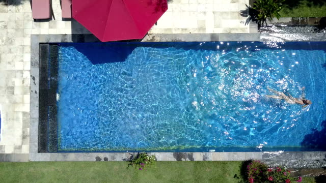 The young beautiful woman swims in the pool in a tropical garden,Aerial view from drone video
