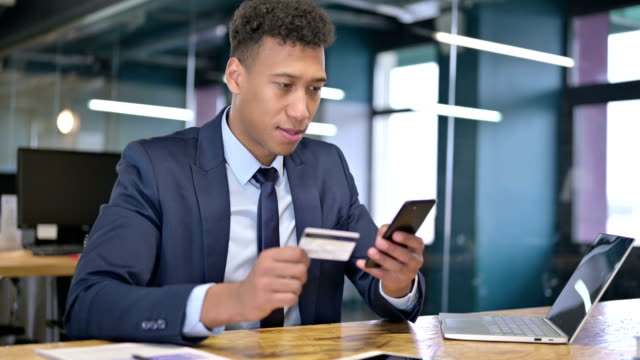 The Young Businessman Celebrating Success on Smartphone
