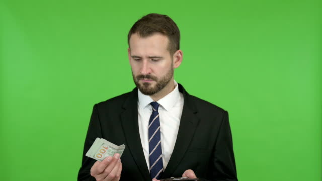 The Young Businessman Showing off Money from Wallet against Chroma key