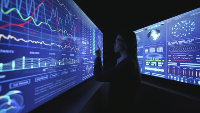 die junge geschäftsfrau arbeitet an einem blauen touchscreen im dunklen labor - medizinisches untersuchungsgerät stock-videos und b-roll-filmmaterial