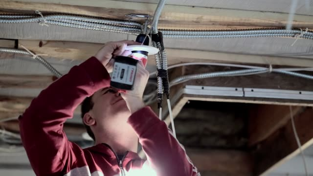 The young electrician installs the electric lamp on the ceiling. video