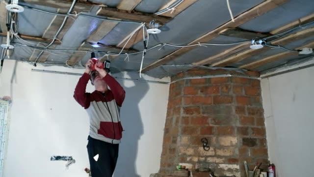 若い電気工事は天井の電気ランプをインストールします。 - 電気工点の映像素材/bロール