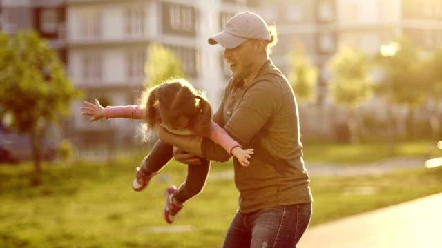 stockvideo's en b-roll-footage met de jonge vader zich omdraait en gooit zijn dochtertje. het meisje lacht vrolijk. een man is het dragen van een baseballcap. gelukkige jeugd. father's day. het cirkelen van het kind. children's day - teenager animal