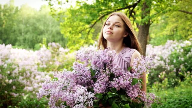 Das junge Mädchen genießt den Duft von Flieder – Video