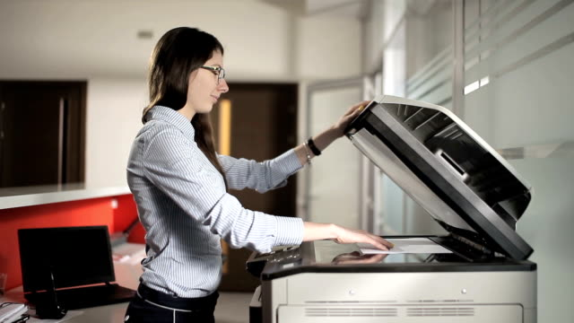 The young girl printing in the office video