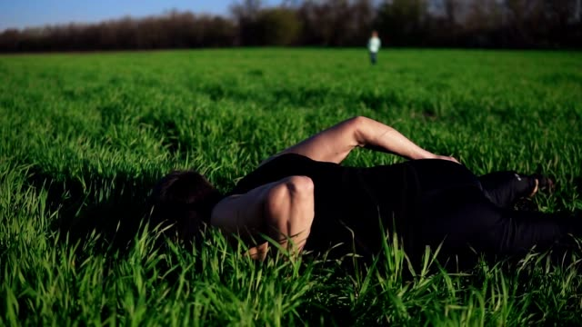 The young guy assiduously does push-ups on one hand. Complicated. Beautiful nature, meadow, clear sky. Overview footage The young guy assiduously does push-ups on one hand. Complicated. Beautiful nature, meadow, clear sky. Overview footage. bodyweight training stock videos & royalty-free footage