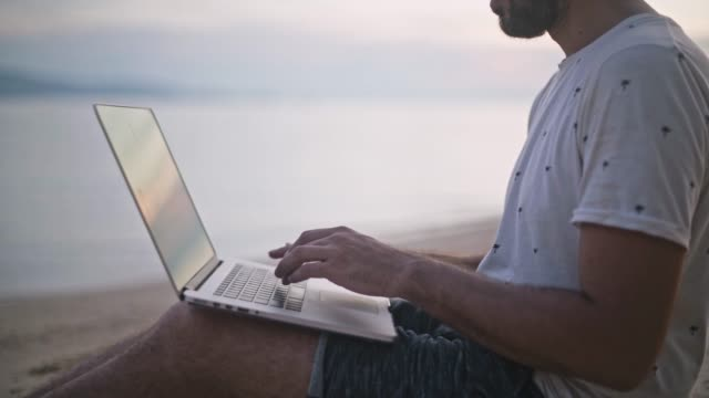 The young, handsome man working on a laptop on the beach in the setting sun.