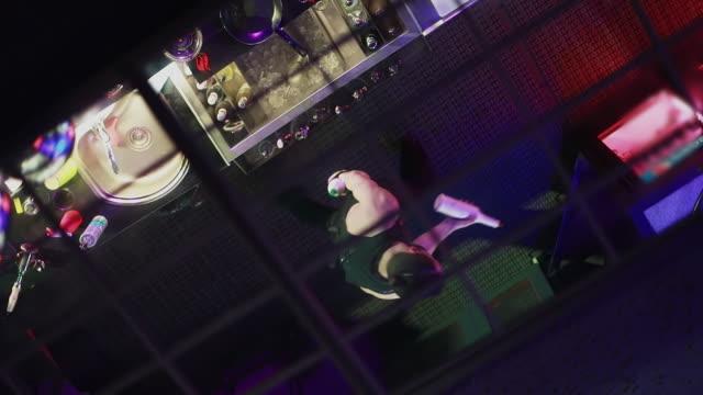 The young man, bartender juggling bottles on a black background. video