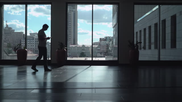 The young man goes down a long corridor room with high windows in which dark and gaining a message on the phone video